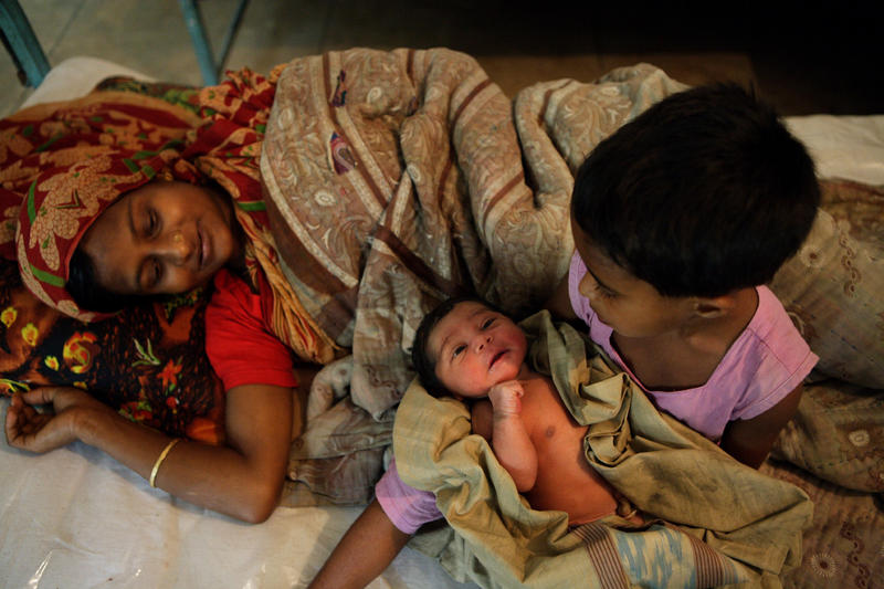 A young girl holds her newborn infant sibling while their mother rests in the EmOC (Emergency Obstetric Care) unit in Upazila Health Complex, Ajmeriganj, Bangladesh.